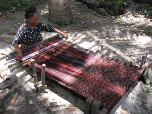 12. The weaving is done on a simple back strap loom. A plain coloured weft is woven into the patterned warp. (640x480)